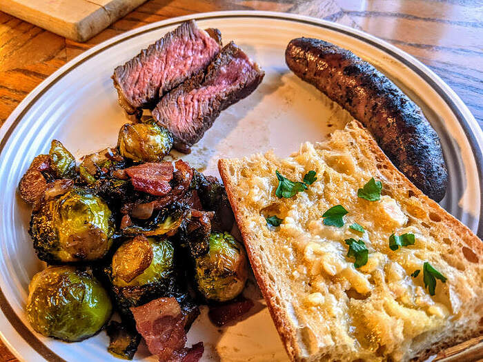 Ribeye brussels sprouts bread sausage plate