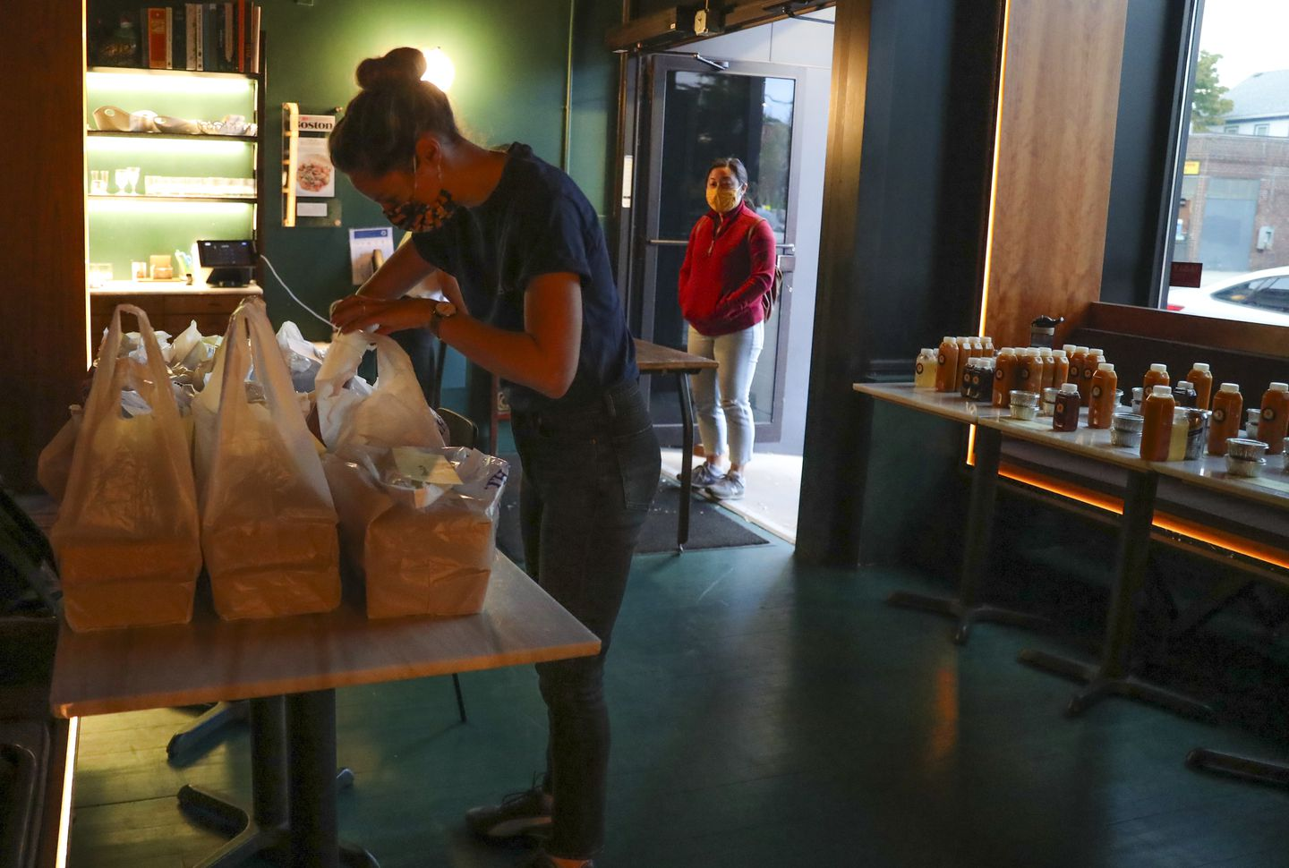 Kate Hardy gets a customer's dinner order ready for pick up at the Sekali pop-up to go at the Fat Hen.